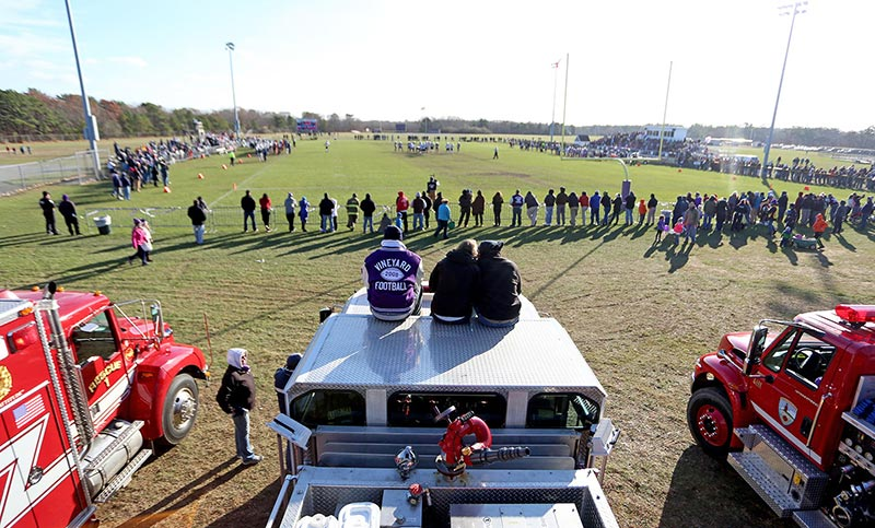 From left, William deBettencourt, Julie Pringle and Josh Baker sit on top of an Edgartown fire truck and watch the Island Cup football game. Trucks from West Tisbury, Oak Bluffs and Edgartown showed up to cheer on the Vineyarders.