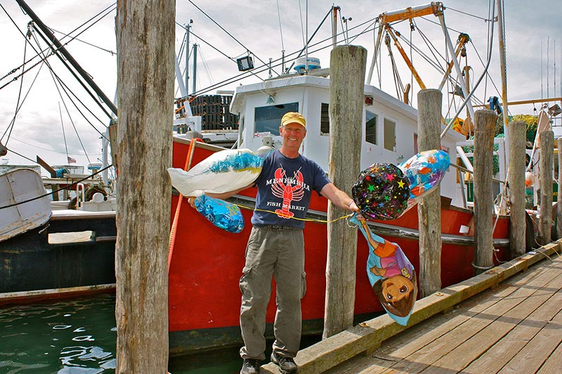 menemsha fisherman cleans up balloons after the party is